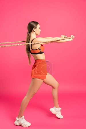 young sportswoman pulling rope while exercising on pink