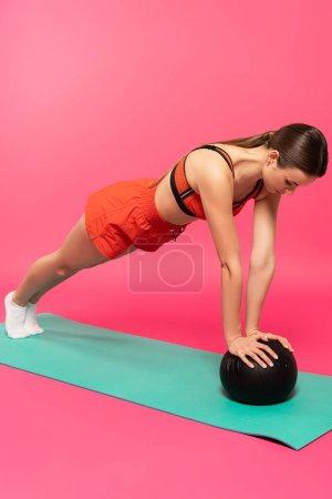 Photo pour Jeune femme en vêtements de sport exercice avec balle sur rose - image libre de droit