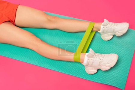 Photo for Cropped view of athletic woman working out with resistance band on fitness mat isolated on pink - Royalty Free Image