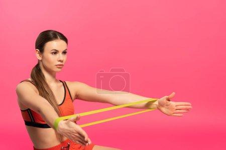 Photo pour Belle sportive travaillant avec bande de résistance sur rose - image libre de droit