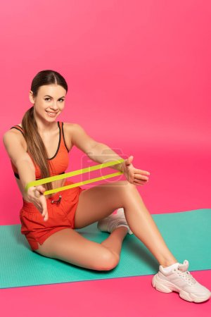 Photo for Happy sportswoman working out on fitness mat with resistance band on pink - Royalty Free Image