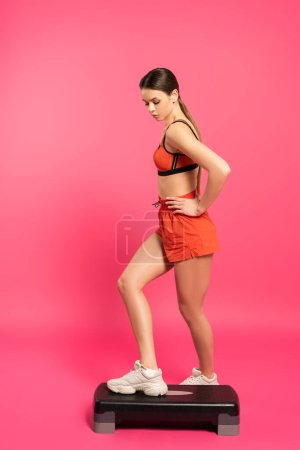 Photo for Sportswoman with hand on hip exercising on step platform on pink - Royalty Free Image