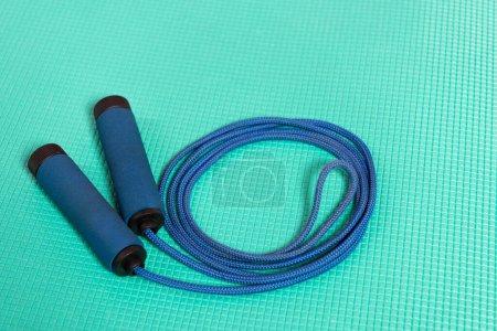 Photo pour Corde à sauter bleue sur tapis de fitness turquoise - image libre de droit
