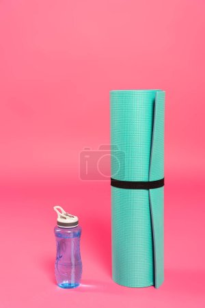 Photo for Sports bottle with water near fitness mat on pink - Royalty Free Image