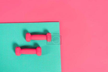 Photo pour Vue de dessus des haltères sur tapis de fitness isolé sur rose - image libre de droit