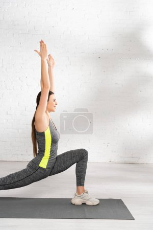 Photo for Side view of happy sportswoman with outstretched hands exercising on fitness mat - Royalty Free Image
