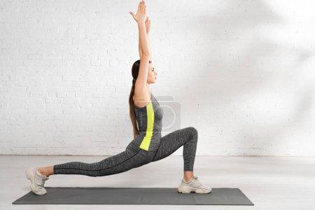 Photo pour Vue latérale de la sportive attrayante avec les mains tendues s'exerçant sur le tapis de fitness - image libre de droit