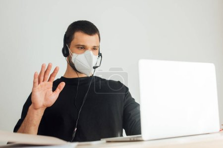 selective focus of operator in medical mask and headset waving hand while having video call at home
