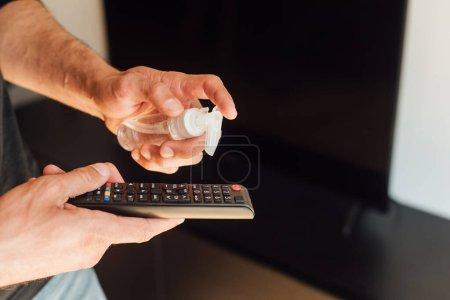 Photo pour Vue recadrée de l'homme tenant bouteille avec désinfectant près de la télécommande - image libre de droit