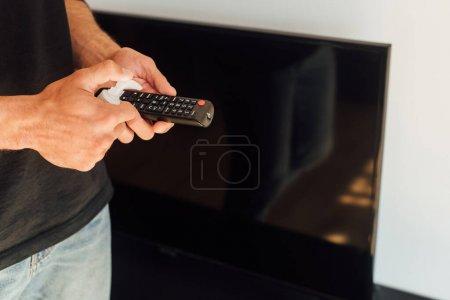 Photo pour Vue recadrée de l'homme tenant bouteille avec un liquide antibactérien près de la télécommande - image libre de droit
