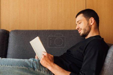 Photo pour Vue latérale du livre de lecture homme beau et barbu dans le salon - image libre de droit