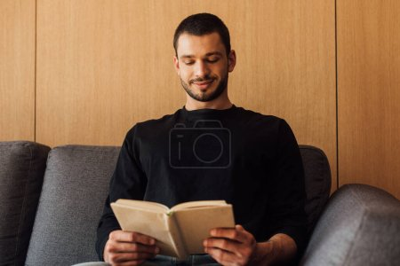 happy and bearded man reading book in living room