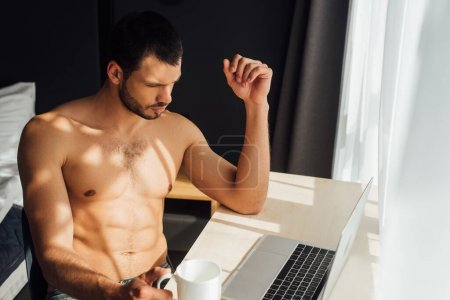 bearded and shirtless freelancer holding cup near laptop at home