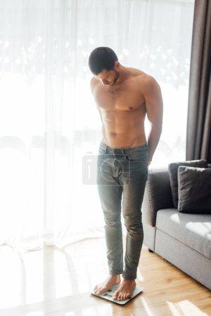 Photo pour Homme musclé debout sur des balances dans le salon - image libre de droit