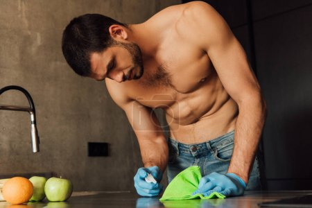Photo for Muscular man in rubber gloves holding rag and bottle with antiseptic near fruits on table - Royalty Free Image