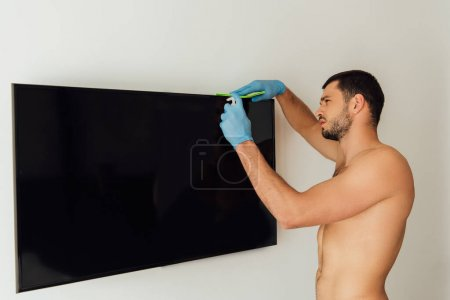 shirtless man in rubber gloves holding rag and bottle with antibacterial liquid near tv with blank screen