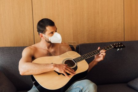 Photo for Muscular man in medical mask playing acoustic guitar in living room - Royalty Free Image