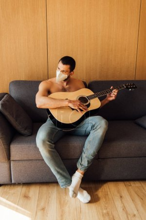 Photo for Shirtless man in medical mask playing acoustic guitar in living room - Royalty Free Image
