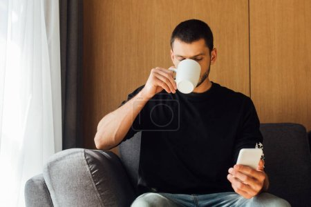 man drinking coffee and using smartphone in living room