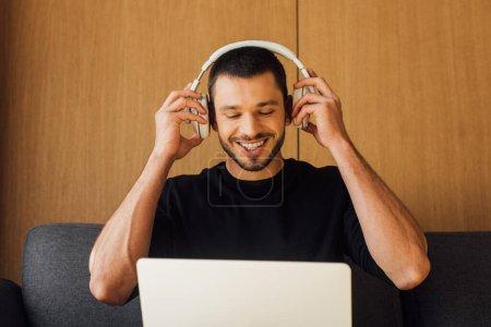 Foto de Feliz freelance portador que toca los auriculares inalámbricos y mira el ordenador portátil. - Imagen libre de derechos