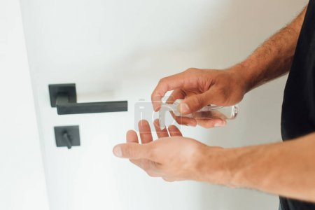 Photo for Cropped view of man holding bottle with hand sanitizer and standing near door - Royalty Free Image