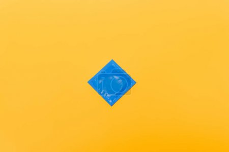 Photo pour Vue de dessus du paquet bleu avec le condom isolé sur orange - image libre de droit