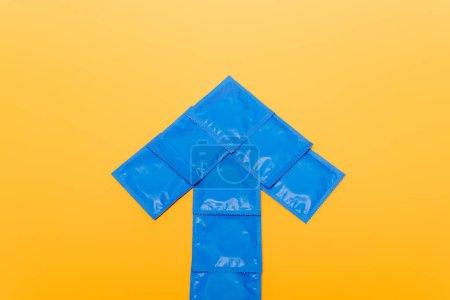 Photo pour Vue du haut de la flèche bleue des paquets avec préservatifs isolés sur orange - image libre de droit