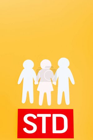 Photo for Top view of three paper people near red paper with std lettering isolated on orange - Royalty Free Image