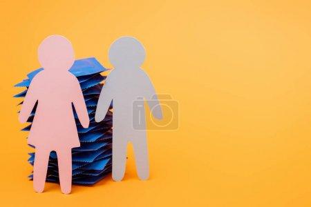 Photo pour Pile de préservatifs près de gens de papier sur orange - image libre de droit
