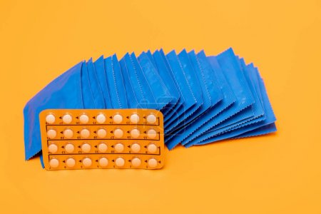 Photo for Blister pack with contraceptive pills near packs with condoms isolated on orange - Royalty Free Image