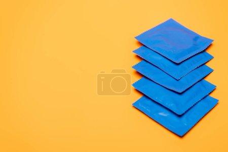 Photo pour Focus sélectif de packs bleus avec préservatifs isolés sur orange avec espace de copie - image libre de droit