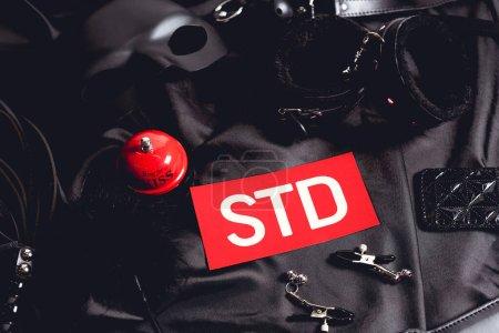 Foto de Vista superior de la campana de sexo rojo cerca del papel con papel con papel picado y juguetes sexuales en negro. - Imagen libre de derechos