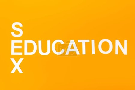 Photo for Top view of white sex education lettering isolated on orange - Royalty Free Image