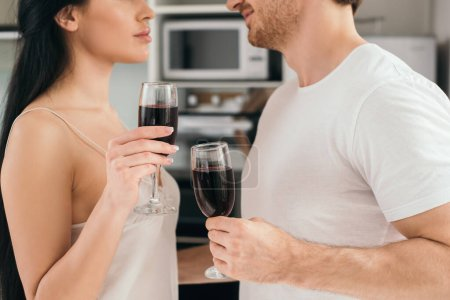 Photo for Cropped view of couple holding glasses with red wine during self isolation at home - Royalty Free Image