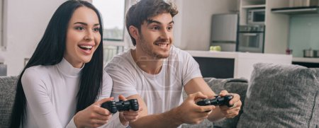Photo for KYIV, UKRAINE - APRIL 16, 2020: beautiful cheerful couple playing video game with joysticks during self isolation at home, website header - Royalty Free Image