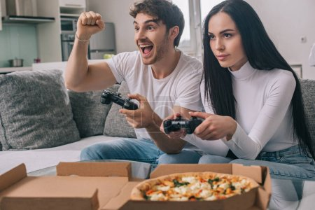 Photo for KYIV, UKRAINE - APRIL 16, 2020: excited couple having pizza and playing video game with joysticks during self isolation at home - Royalty Free Image