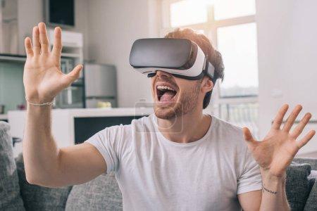 Photo pour Excité homme utilisant casque de réalité virtuelle à la maison sur l'isolement de soi - image libre de droit