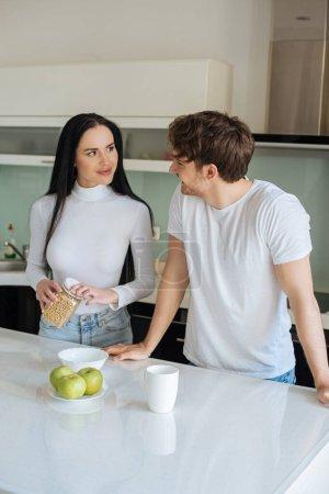 junges schönes Paar mit Cornflakes zum Frühstück während der Selbstisolierung zu Hause