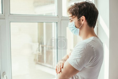 Photo for Sad ill man in medical mask with crossed arms looking through window during self isolation - Royalty Free Image