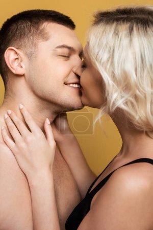 Photo pour Vue latérale du couple souriant s'embrassant sur fond jaune - image libre de droit