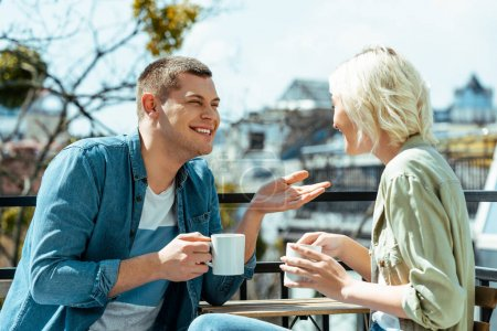 Photo for Smiling couple talking and drinking tea on terrace - Royalty Free Image