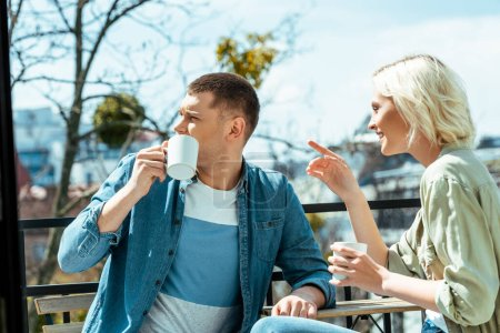 smiling couple talking and drinking tea on terrace while woman pointing with finger away