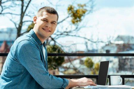 Photo pour Freelance souriant assis sur la terrasse avec ordinateur portable et papiers - image libre de droit
