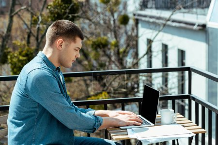 freelancer sitting on terrace with laptop and papers