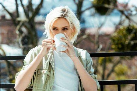 Foto de Chica rubia sentada en la terraza con jarra - Imagen libre de derechos
