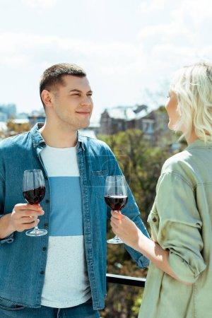 Foto de Pareja sonriente con vino tinto en terraza soleada. - Imagen libre de derechos