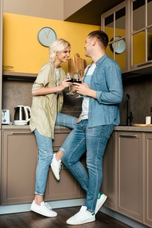 Photo for Smiling couple drinking red wine together in kitchen - Royalty Free Image