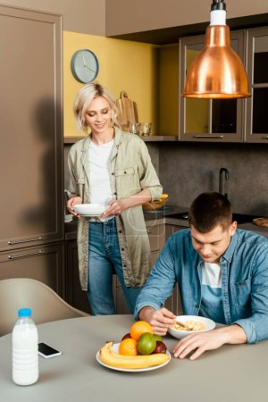 Photo for Smiling couple having breakfast with cereal and fruits in kitchen - Royalty Free Image