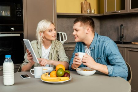 Photo for Woman showing digital tablet to husband while having breakfast in kitchen - Royalty Free Image