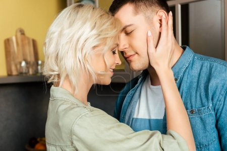 smiling young loving couple hugging at home